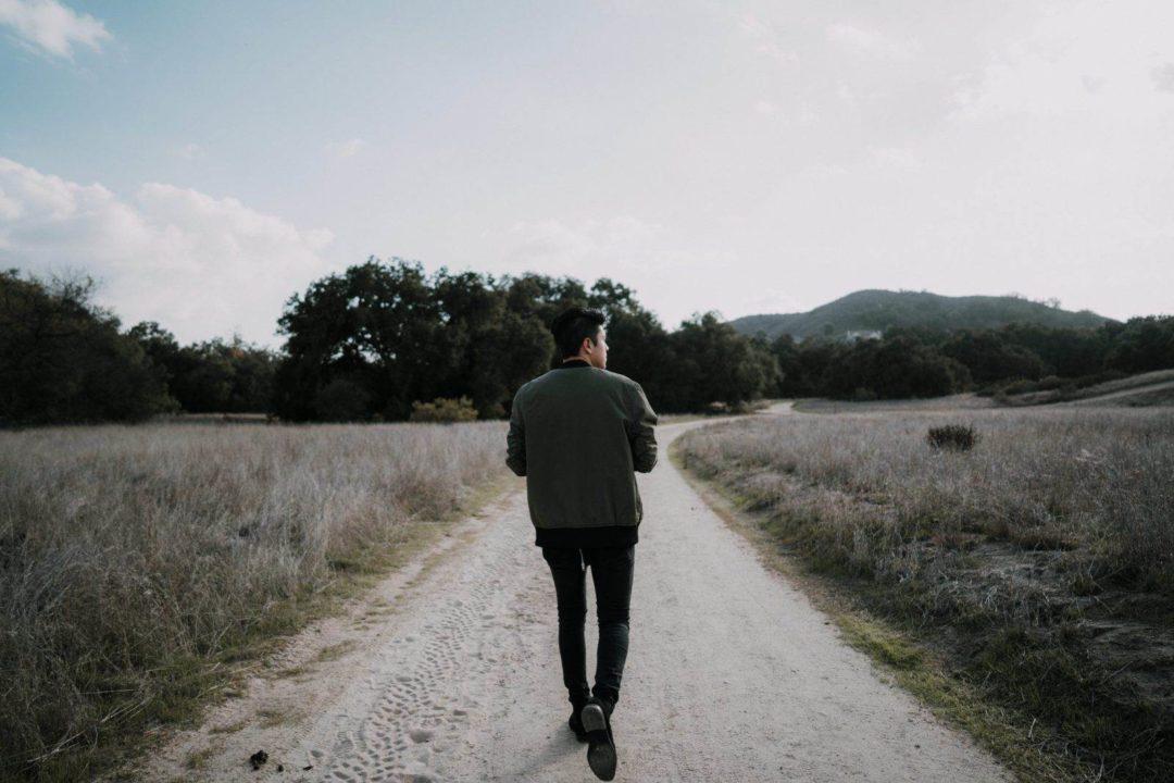 man walking down path
