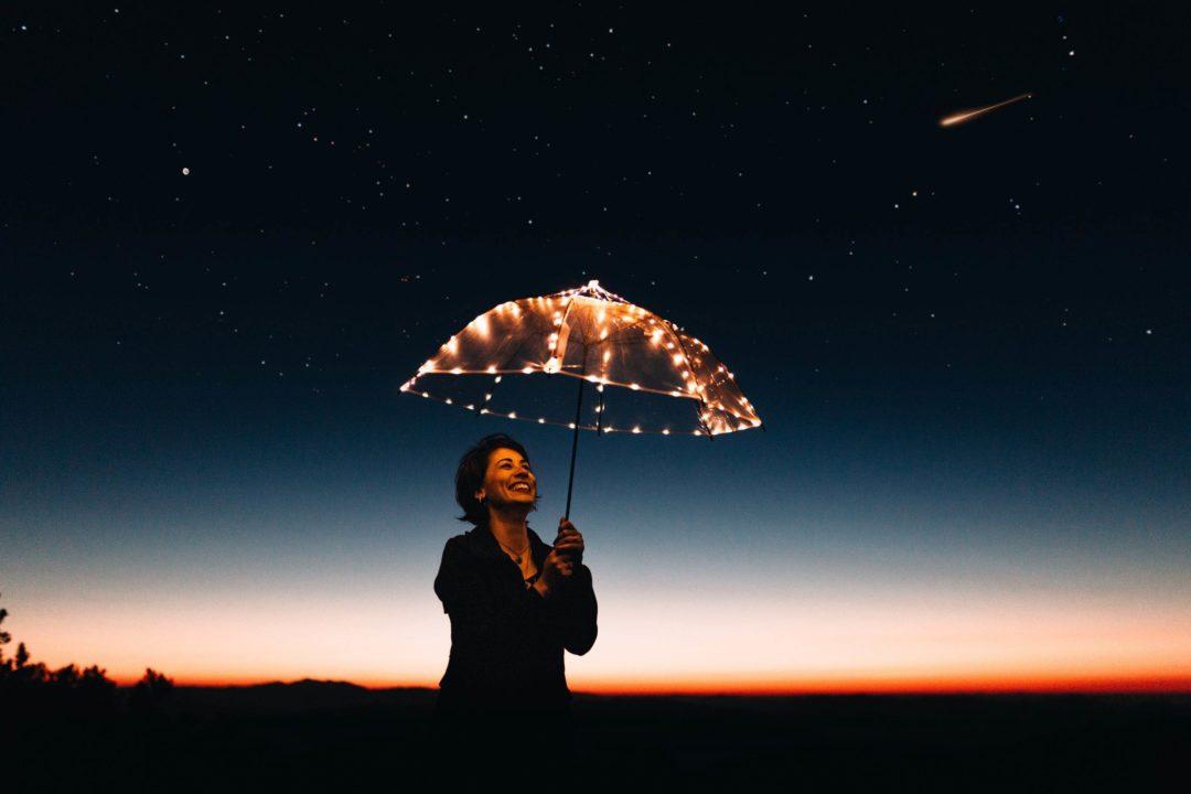 Women with a light up umbrella under the stars