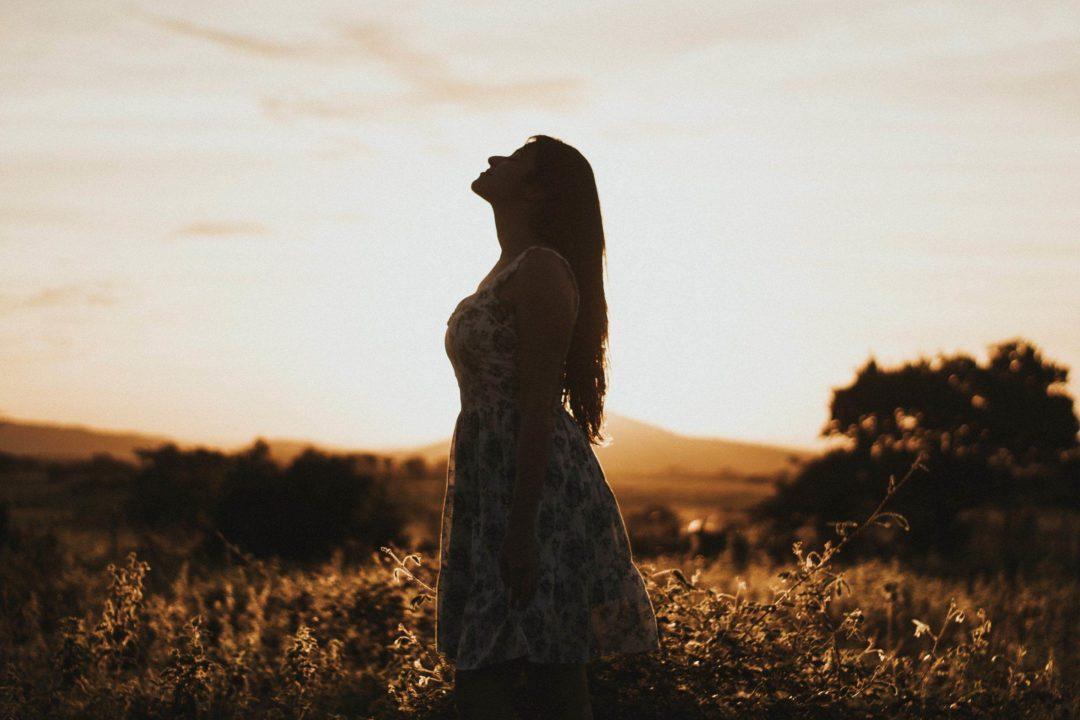 woman in meadow soaking up the sun