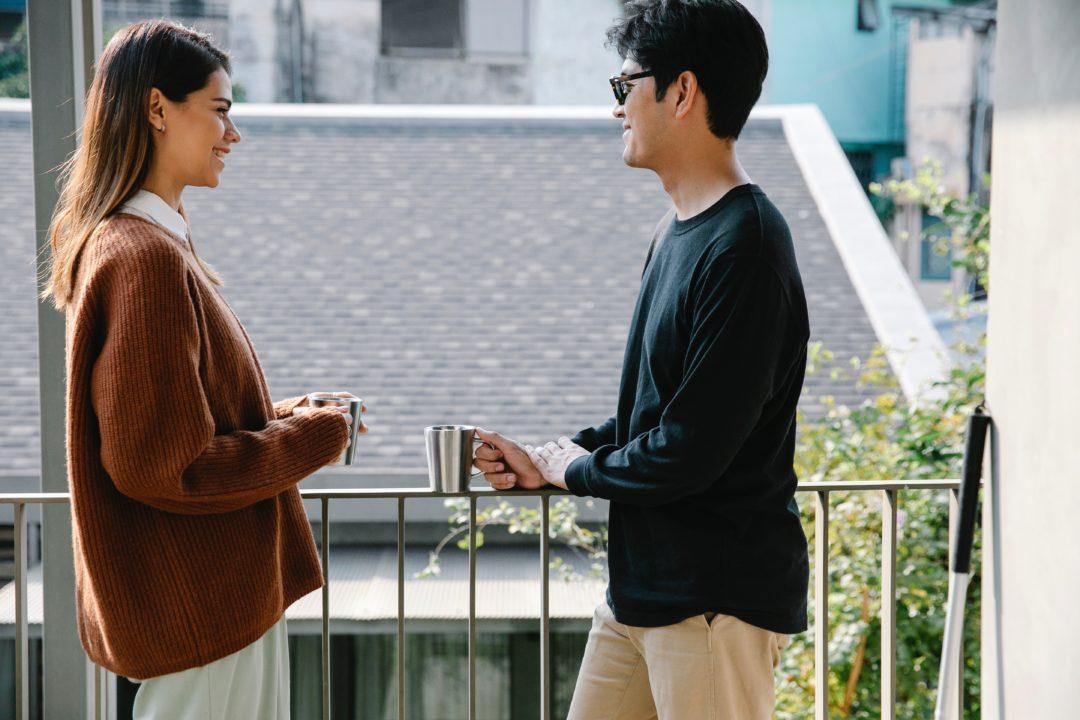 adult couple talking on balcony
