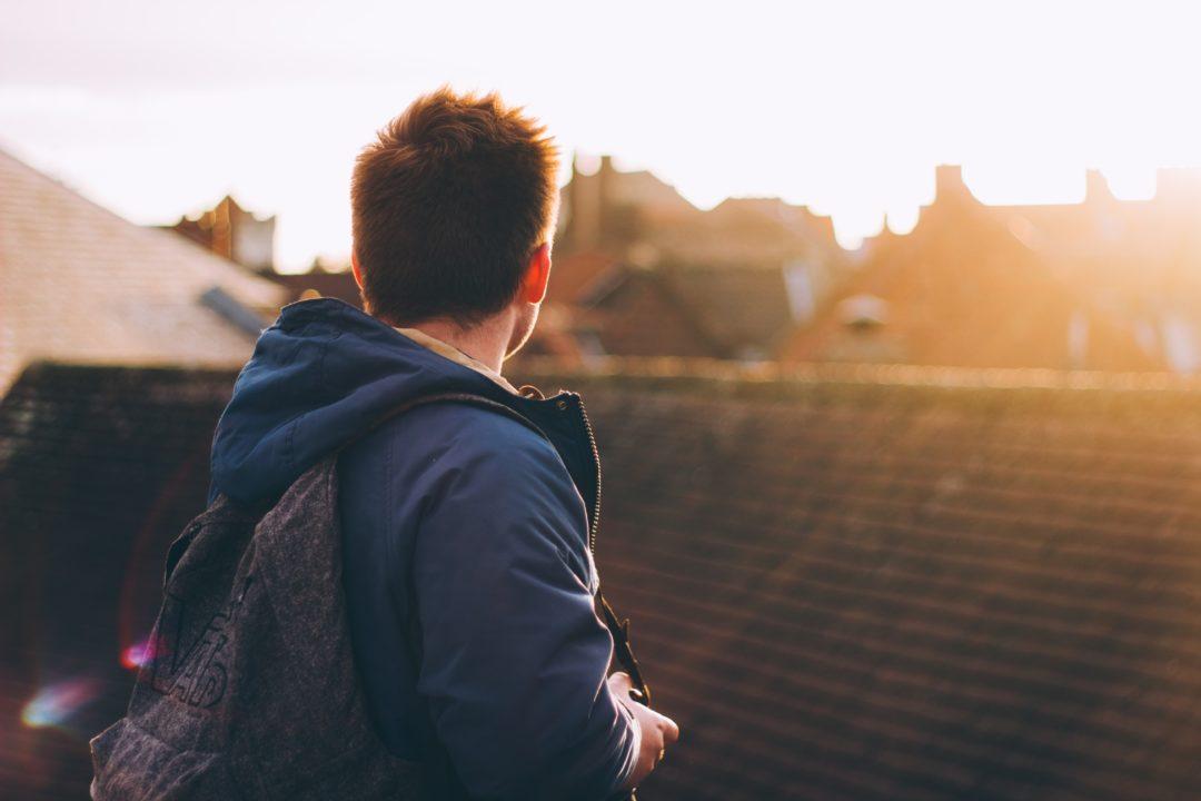 man looking at sunrise