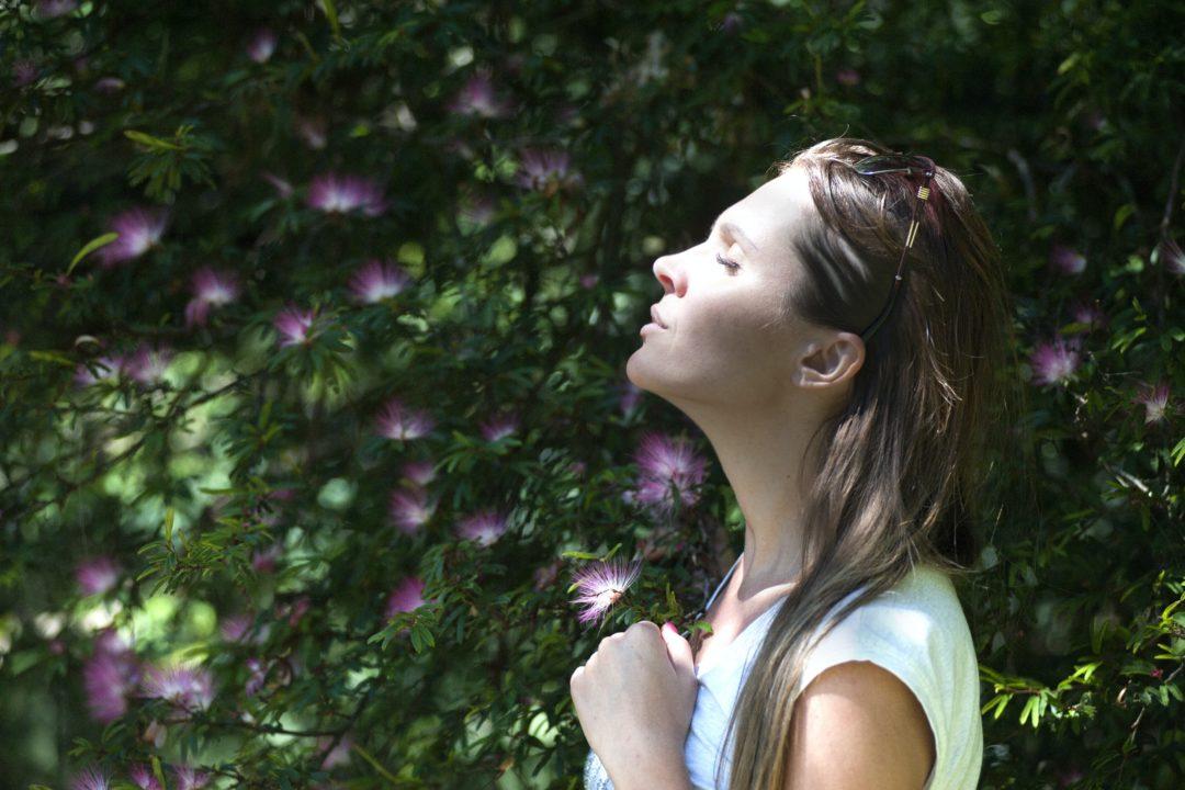woman breathing by flowers