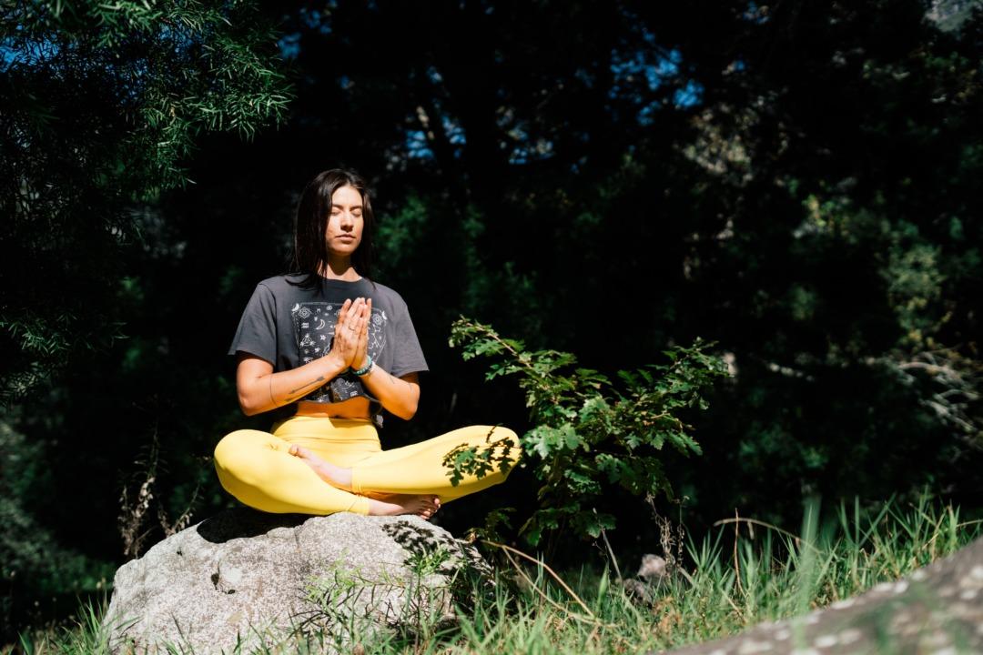 woman doing yoga on a rock